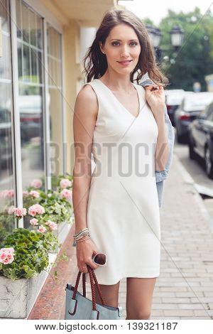 Pretty brunette lady in white elegant dress on city street background