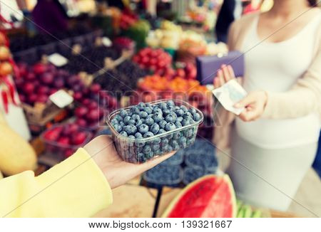sale, shopping, pregnancy and people concept - close up of pregnant woman with wallet and money buying blueberry at street food market