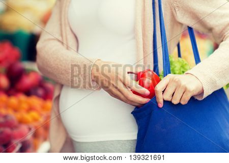 sale, shopping, food, pregnancy and people concept - close up of pregnant woman buying red pepper or paprika at street market