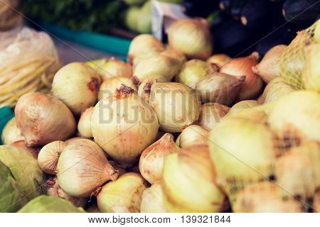 sale, harvest, food, vegetables and agriculture concept - close up of onion at street market