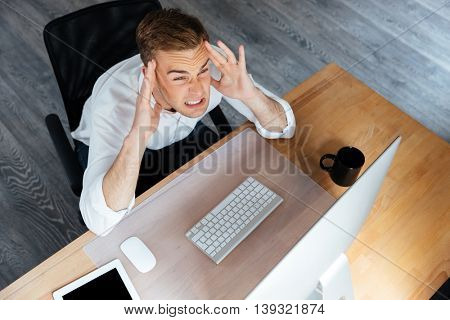 Top view of stressed young businessman working with computer and having a headache in office