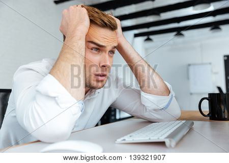 Upset disappointed young businessman sitting at workplace with hands on head