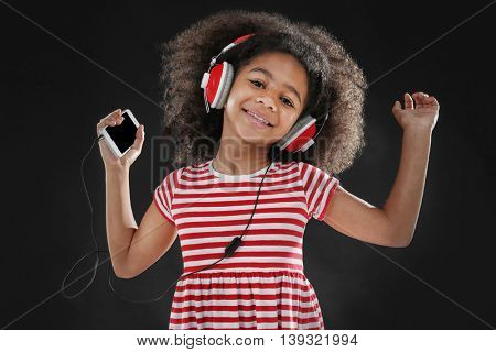 Afro-American little girl with headphones on dark background
