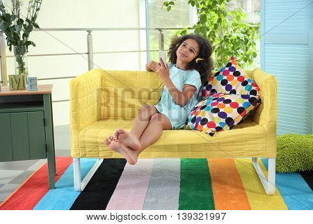 Afro-American little girl with headphones and smartphone on sofa in  room