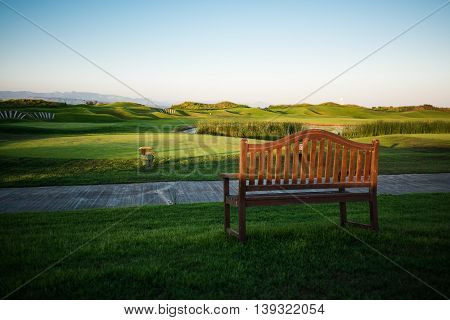 Walkway with bench near golf course with trees on background at sunset