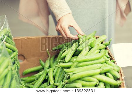 sale, shopping, food, vegetables and people concept - close up of woman hand choosing green peas at street market