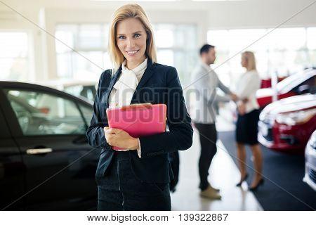 Professional young saleswoman working at car dealership