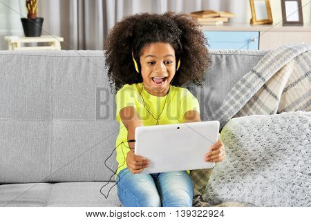 Afro-American little girl with headphones and tablet on sofa in room