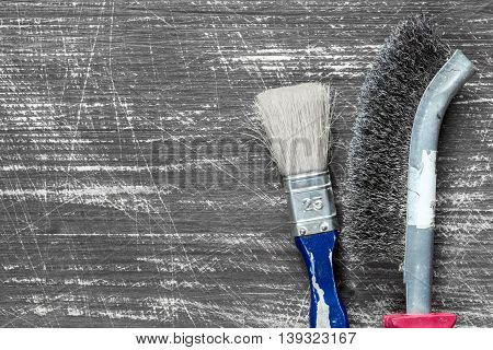 Paintbrush and wire brush on the wooden background with copy-space