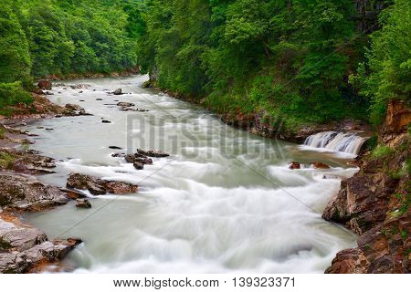 Wild river with a small waterfall in the forest.