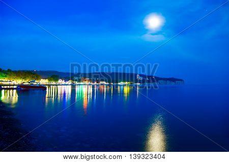Night coast. Boat. Moon. Sea. The lights of the city.