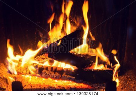 heating, warmth, fire and cosiness concept - close up of firewood burning in fireplace