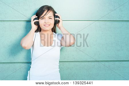 Girl Holding Headphones And Enjoying Listening To Music