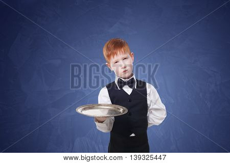 Little sad and tire waiter stands with empty tray serving. Redhead child boy in suit plays hardworking restaurant servant at blue background