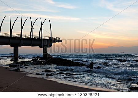 Man performing religious ritual next to the Millennium Pier in Umhlanga Rocks at Sunrise with ships on the Indian Ocean in the background