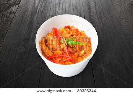 Mexican cuisine food delivery - chili con carne in white plastic plate closeup at black wood background