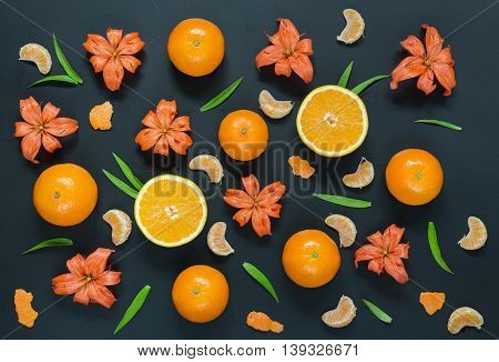 Pattern with lily flowers oranges and mandarines on black background. Flat lay top view