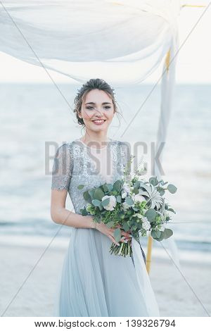Gorgeous bride with wedding bouquet by the sea.