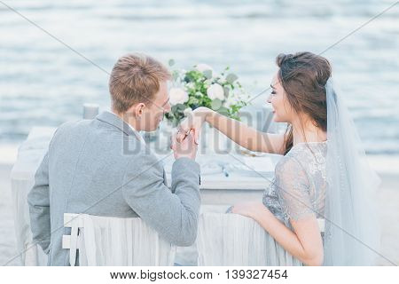 Groom wishing to kiss bride's hand at the seashore.