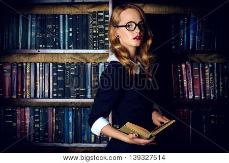 Beautiful girl wearing old-fashioned  black dress and spectacles stands in the old library. Retro style. Beauty, fashion.