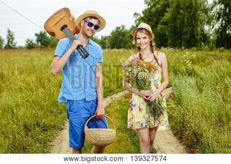 Beautiful couple in love walking along a country road on a sunny summer day. They are happy. Love concept.