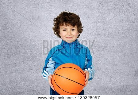 Smiling boy with six years old with a basket ball looking at camera