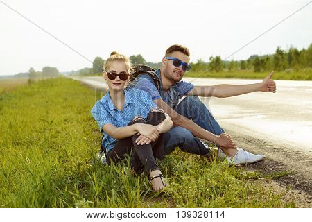 Hitchhiking couple. Happy young people sitting by the highway.