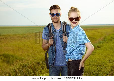 Hitchhiking couple. Happy young people standing by the highway.