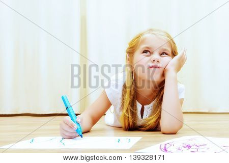 Cute girl lying on a floor and drawing on a paper with colorful pens.