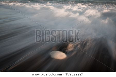 Sea waves crashing into the shore and flowing above a white pebble. Long exposure photography