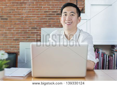 Handsome Asian Businessman With Computer In Cafe (focus On Face)