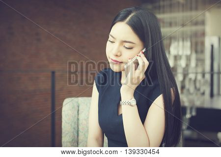 Asian Business Woman Talking On The Phone With Unhappy Or Stressful Look In Office Background (vinta