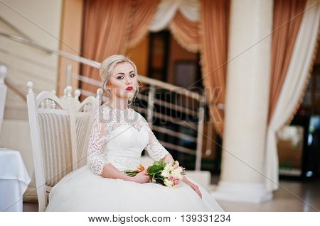 Gorgeous Blonde Bride With Wedding Bouquet At Hand Sitting At Great Wedding Hall
