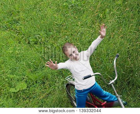 Young girl is cycling into on a green meadow raised her hands up.