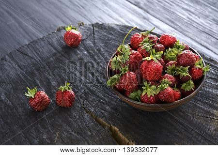 Red fresh strawberries on black rustic wood background. Bowl with natural ripe organic berries with peduncles on wooden circle cut out