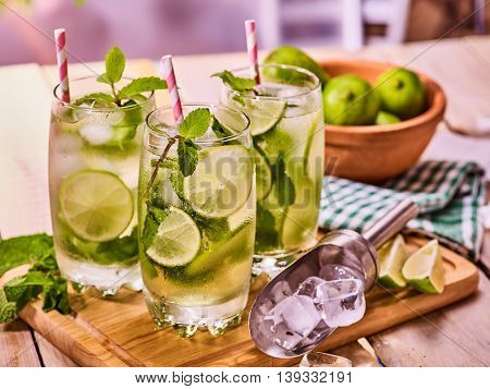 Alcohol cocktail. On wooden boards three glasses with alcohol cocktail and ice cubes. Drink number hundred and ninety two cocktail mohito with straw and lime and mint leaf. Country life. Indoor.