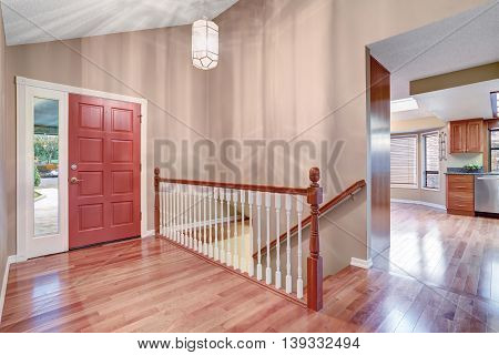 Simple Entry Way With Hardwood Floor And Staircase.