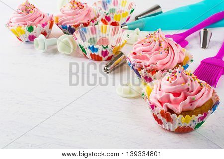 Pink birthday cupcakes and cookware background. Birthday cupcake with pink whipped cream. Homemade cupcakes decorated for party.