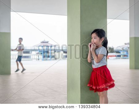 cute girl playing hide and seek with her brother
