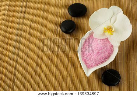 Spa concept with pink sea salt and spa stones. Spa treatment concept. Wellness still life.