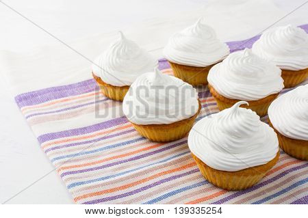 White birthday cupcakes on the striped linen napkin. Homemade cupcakes with whipped cream. Birthday party cupcakes.