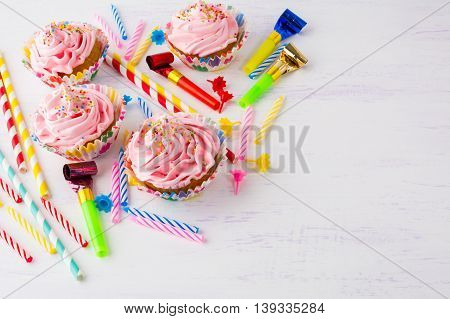 Birthday background with pink cupcakes and birthday candles. Homemade cupcakes with whipped cream. Holiday party background.