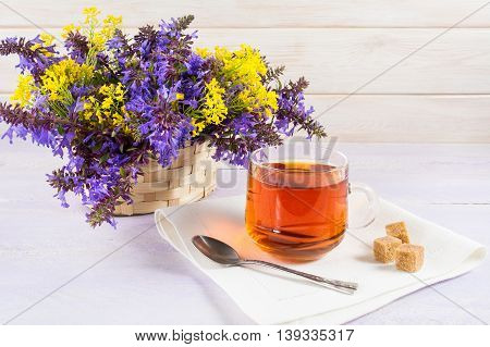 Cup of tea and wicker basket with purple and yellow flowers. Spring tea time concept. Breakfast tea cup served with flowers.