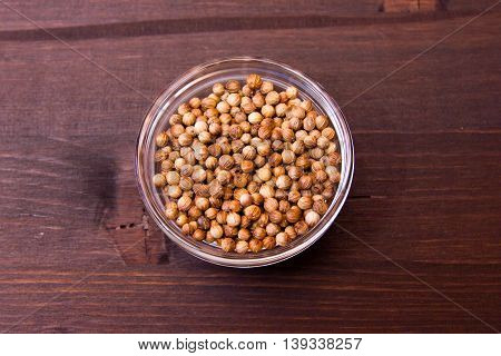 Coriander seeds on a bowl on a wooden table seen from above