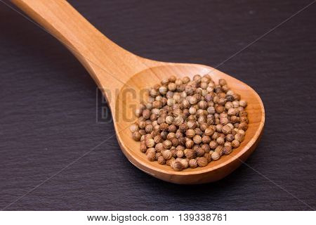 wooden spoon with coriander seeds on a slate floor