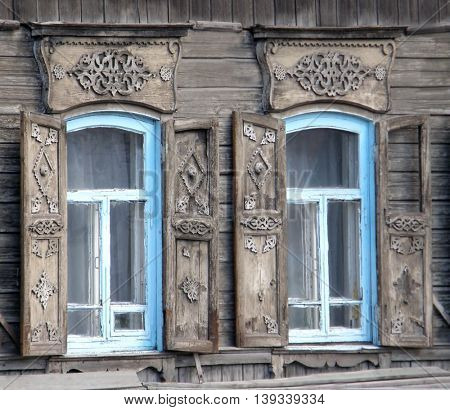 The windows with beautiful architraves in old wooden house. Ulan-Ude. The Republic of Buryatia.