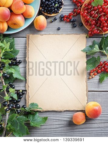 Healthy eating background. Old paper with fresh apricots, bilberry and currants on wooden table. Top view, high resolution product. Harvest concept.