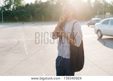 Side view of cheerful young woman talking on cell phone walkin with bright sunlight outdoors.