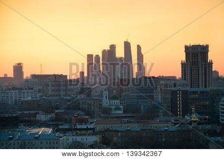 Panorama of roofs, domes of churches and skyscrapers during sunset in Moscow