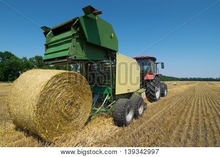 Green modern tractor makes big straw roll on yellow field at summer day